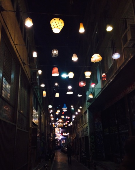 An alleyway lit with recycled containers of all sorts